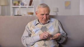 Hombre envejecido triste que se sienta en el sofá y que cuenta monedas en la palma, inseguridad social metrajes