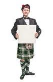 Hombre escocés en traje nacional tradicional con la bandera vacía Imagenes de archivo