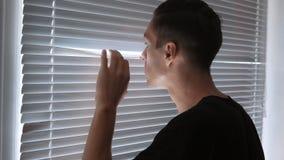 Hombre, espía, periodista o detective paranoico, relojes a través de las persianas almacen de metraje de vídeo