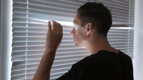 Hombre, espía, periodista o detective paranoico, relojes a través de las persianas metrajes