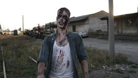 Hombre espeluznante del zombi en ropa sangrienta que camina por las líneas ferroviarias al aire libre con un lugar abandonado ind almacen de metraje de vídeo