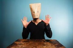 Hombre estúpido con el bolso sobre su cabeza y manos para arriba Foto de archivo libre de regalías