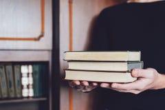 Hombre, estudiante que sostiene muchos libros en manos en el fondo de estantes Las manos masculinas sostienen una pila grande de  fotos de archivo