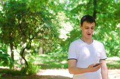 Hombre europeo sorprendido que mira en el teléfono y la sonrisa dependencia del teléfono, redes sociales Trabajo sobre el Interne Imágenes de archivo libres de regalías