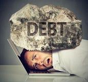 Hombre exprimido entre el ordenador portátil y la roca Concepto de la deuda crediticia del estudiante imagen de archivo