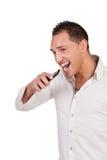 Hombre extático que lleva a cabo un móvil y una risa Fotografía de archivo