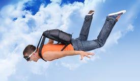Hombre extremo del vuelo con un paracaídas en las nubes Foto de archivo