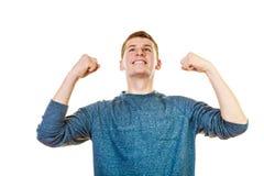 Hombre feliz acertado con los brazos para arriba que aprietan el puño Foto de archivo