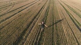 Hombre feliz acertado joven que corre en el campo, brazos extendidos Visión panorámica aérea metrajes