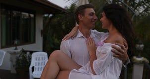 Hombre feliz Carry Woman Out On Terrace en la puesta del sol, par romántico en amor besándose sobre paisaje tropical metrajes