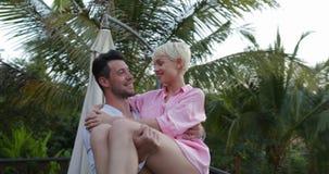 Hombre feliz Carry Woman On Summer Terrace en la puesta del sol, par romántico en amor durante luna de miel metrajes