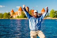 Hombre feliz cerca del castillo y del lago Foto de archivo