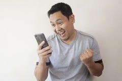 Hombre feliz chocado que mira el tel?fono elegante foto de archivo libre de regalías