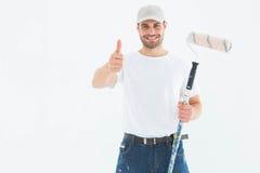 Hombre feliz con el rodillo de pintura que gesticula los pulgares para arriba Fotos de archivo libres de regalías