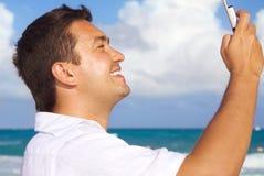 Hombre feliz con el teléfono en la playa Fotos de archivo libres de regalías
