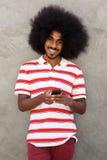 Hombre feliz con el teléfono móvil que se coloca con afro Imagen de archivo