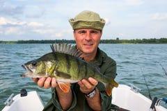 Hombre feliz con el trofeo grande de la pesca de la perca Fotos de archivo