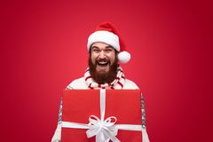 Hombre feliz con la barba que hace sorpresa con la caja de regalo roja foto de archivo libre de regalías