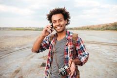 Hombre feliz con la cámara de la foto del vintage que habla en el teléfono móvil Foto de archivo