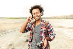 Hombre feliz con la cámara de la foto del vintage que habla en el teléfono móvil Fotos de archivo libres de regalías
