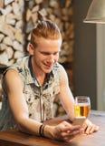 Hombre feliz con la cerveza de consumición del smartphone en la barra Fotografía de archivo