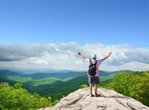 Hombre feliz con las manos aumentadas encima de la montaña Imagenes de archivo
