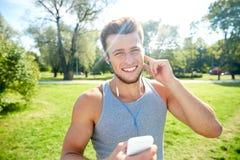 Hombre feliz con los auriculares y smartphone en el parque Foto de archivo libre de regalías