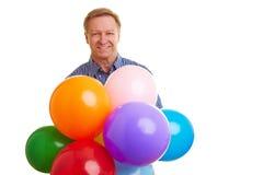 Hombre feliz con los globos coloridos Foto de archivo libre de regalías