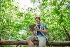 Hombre feliz con PC de la mochila y de la tableta en bosque Foto de archivo