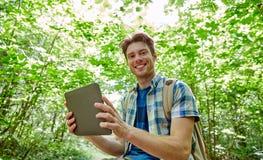 Hombre feliz con PC de la mochila y de la tableta en bosque Fotos de archivo