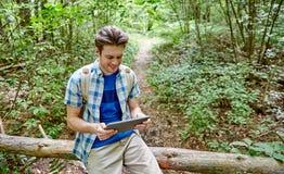 Hombre feliz con PC de la mochila y de la tableta en bosque Imágenes de archivo libres de regalías