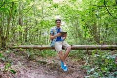 Hombre feliz con PC de la mochila y de la tableta en bosque Fotografía de archivo libre de regalías