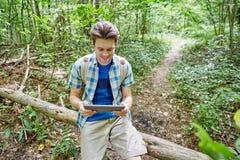 Hombre feliz con PC de la mochila y de la tableta en bosque Imagenes de archivo