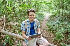 Hombre feliz con PC de la mochila y de la tableta en bosque Imagen de archivo