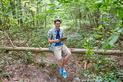 Hombre feliz con PC de la mochila y de la tableta en bosque Foto de archivo libre de regalías