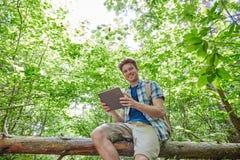 Hombre feliz con PC de la mochila y de la tableta en bosque Fotos de archivo libres de regalías