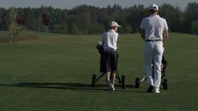 Hombre feliz con sus golfistas del hijo que caminan en campo de golf perfecto en el día de verano almacen de video