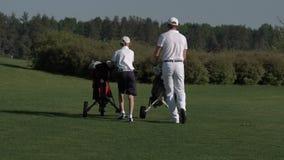 Hombre feliz con sus golfistas del hijo que caminan en campo de golf perfecto en el día de verano metrajes