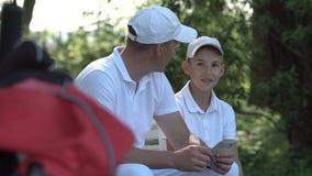 Hombre feliz con sus golfistas del hijo que caminan en campo de golf perfecto en el día de verano almacen de metraje de vídeo