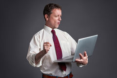 Hombre feliz con una computadora portátil Fotos de archivo libres de regalías