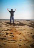 Hombre feliz de la libertad que se coloca en la playa Imagenes de archivo
