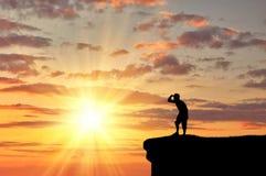 Hombre feliz de la silueta en el top de la montaña Imagen de archivo
