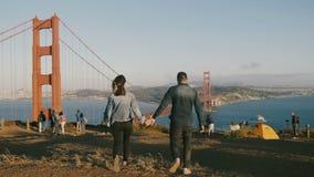 Hombre feliz de la visión trasera y paseo de la mujer juntas que lleva a cabo las manos en la hermosa vista épica de puente Golde almacen de metraje de vídeo