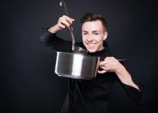 Hombre feliz del cocinero que hace la sopa deliciosa Fotografía de archivo