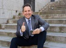 Hombre feliz del empresario de negocio maduro que sienta al aire libre las escaleras urbanas que trabajan y que usan el teléfono  foto de archivo