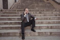 Hombre feliz del empresario de negocio maduro que sienta al aire libre las escaleras urbanas que trabajan y que usan el teléfono  imagenes de archivo