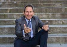 Hombre feliz del empresario de negocio maduro que sienta al aire libre las escaleras urbanas que trabajan y que usan el teléfono  imagen de archivo libre de regalías