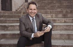 Hombre feliz del empresario de negocio maduro que sienta al aire libre las escaleras urbanas que trabajan y que usan el teléfono  imagen de archivo