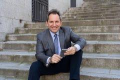 Hombre feliz del empresario de negocio maduro que sienta al aire libre las escaleras urbanas que trabajan y que usan el teléfono  fotografía de archivo libre de regalías