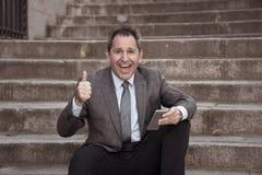 Hombre feliz del empresario de negocio maduro que sienta al aire libre las escaleras urbanas que trabajan y que usan el teléfono  imágenes de archivo libres de regalías